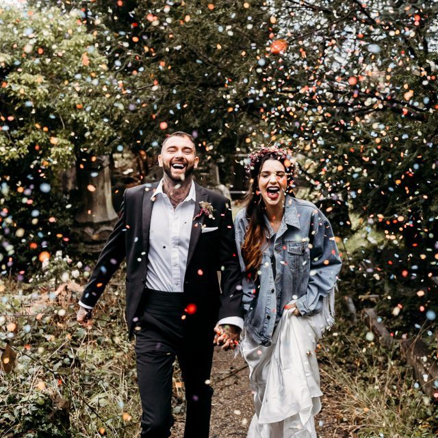 alternative bride and groom walking through confetti tunnel