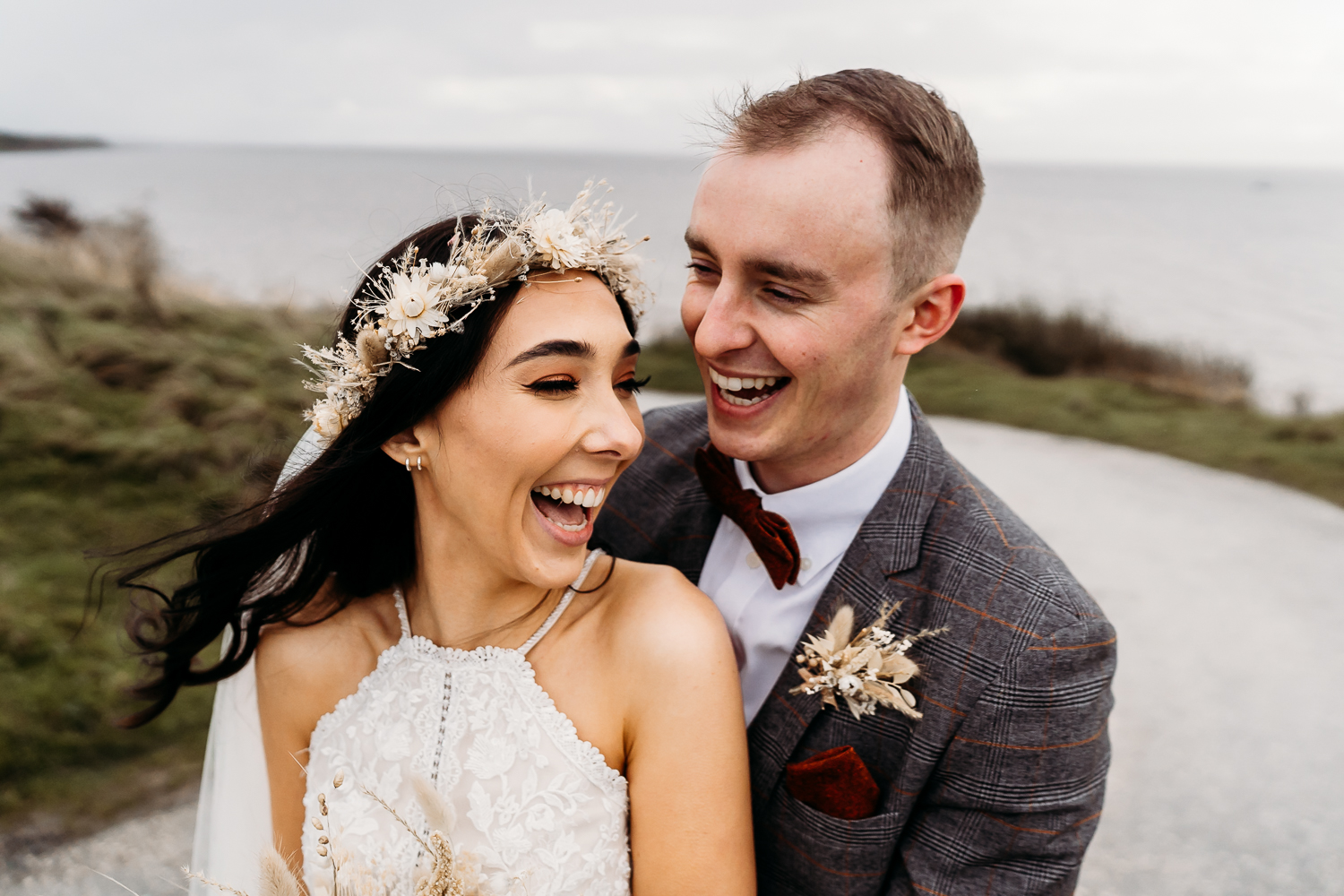 fun young bride and groom hugging at liverpool beach