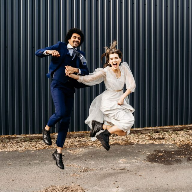 alternative bride and groom jumping in air after cripps and co wedding